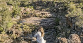 Woman photographing a deep gorge with waterfalls in the mid ground